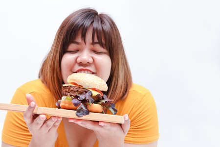 Fat Asian women eat large hamburgers, white background. Health concept. People who are overweight.