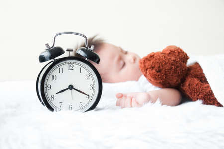 The little boy slept in bed with a teddy bear sleeping as a friend. He is sick with a cold. The morning clock at 8.20 a.m. Childcare Concept Foto de archivo