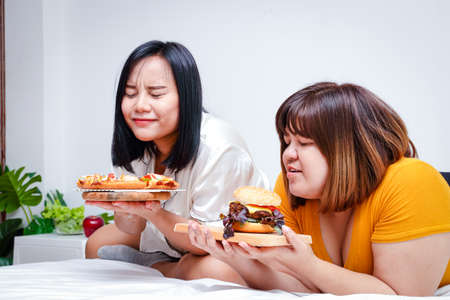 Two fat girls eat pizza and hamburgers in bed in the bedroom. Happy. The concept of eating and health care.