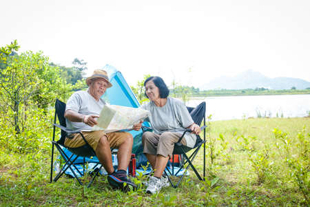 Happy asian senior couple Camping at the waterfront, sitting on a chair, view tourist map, with copy space. Stock Photo