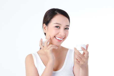 Asian women love health, have fair skin, clean and beautiful, apply body cream, white background. Beauty concept