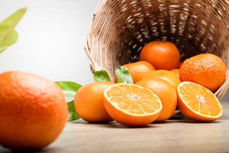Many fresh oranges in a wooden basket placed on the floor. There are some balls that are cut in half to make them look appetizing. Healthy food concept, vitamin C.