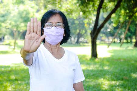 Elderly women wear purple cloth masks, raise your hands, do not get close to prevent the spread of the virus. Coronavirus Prevention Concept, Social Distance