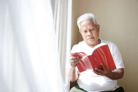 An elderly Asian man sat down beside the window in the bedroom to read. The concept of life in retirement