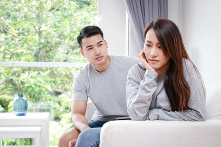 Asian couples quarreling with their wives, feeling sad, do not trust their husbands to talk, do not know about. Married couple concept