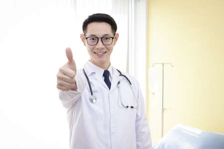 The Asian doctor raised a thumbs up and was confident in treating the patient. Hospital concept