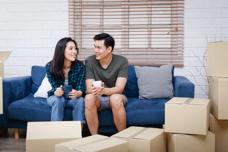 An Asian couple sits on a sofa and just moved into a new home to create a warm family. It's the beginning of a couple life. Copy space