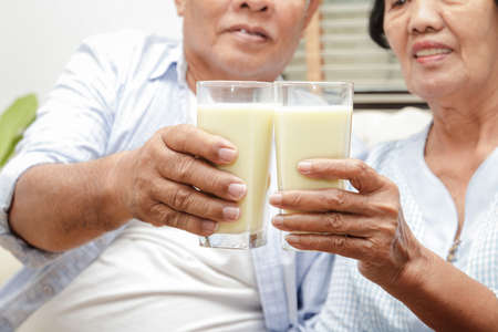 An elderly Asian couple drinks calcium-rich milk to prevent osteoporosis. Make the body strong and healthy