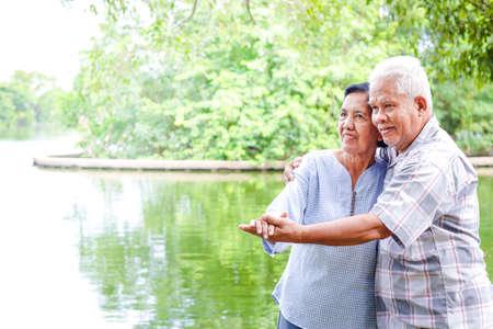 Elderly lovers holding hands dancing in the garden Have fun in retirement life. Senior community concepts 版權商用圖片