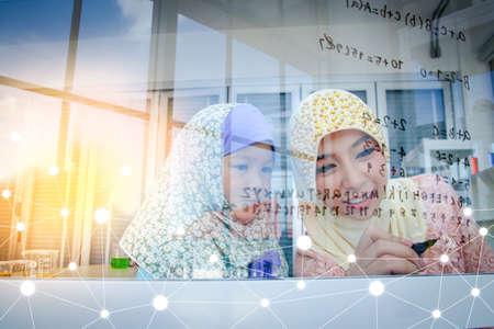 Islamic female teacher taught mathematics to a little girl in the classroom. The concept of children's education Foto de archivo