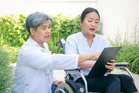 Doctors advise on choosing a health check program. Of female patients sitting on a wheelchair Zdjęcie Seryjne