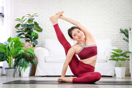 Fitness women doing yoga, difficult postures in the white living room at home. Healthy exercise concept. Advanced yoga postures