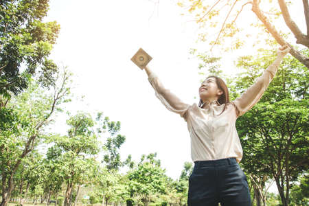 A woman working in a office holding a trophy Raise both hands, happy