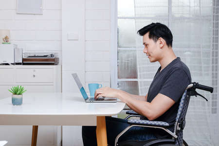 Asian disabled men Ride in a wheelchair Working on a laptop computer At the office in his home. Copy space