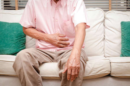 Elderly men have abdominal pain sitting on the sofa in the house. Concept Stock Photo