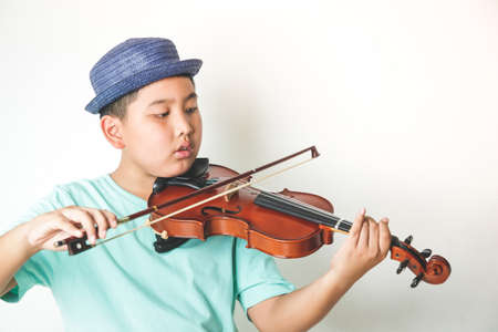 Asian boy playing violin instrument