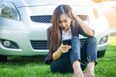 Beautiful woman, her car is broken She sat with the phone for help.