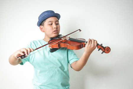 The little Asian boy wearing a hat is playing and practicing the violin in the white room.