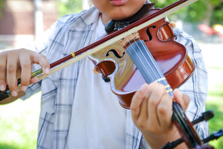 Boy playing violin music. He is happy.