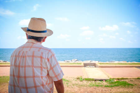 An elderly man wearing a hat looking at the beautiful sea