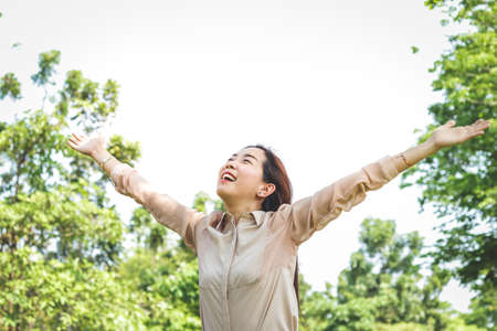 A beautiful Asian woman is an office worker. She spread both arms happy. Banco de Imagens