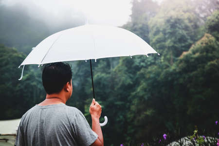 Men holding a white umbrella when it rains Come to visit nature, fresh air, cool