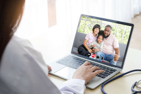 A woman doctor chatting over an online video call with an African-American family of patients. Concept of communicating through technology online. Doctors can examine patients through video calls.