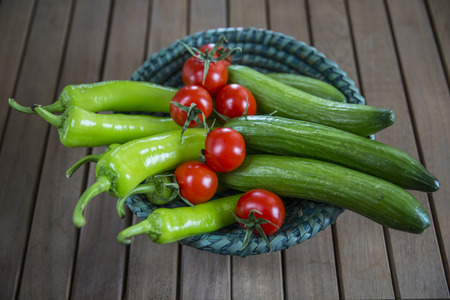 Tomatoes, cucumbers and peppers in basket on wooden background.