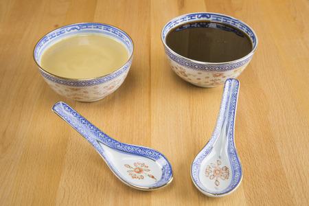 ajonjoli: Melaza y tahini de sésamo pasta de porcelana en un recipiente de porcelana con cuchara. Foto de archivo
