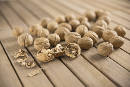 Walnut kernels and whole walnuts on wooden background. Stock Photo