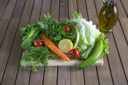 Fresh vegetables and olive oil on wooden background.
