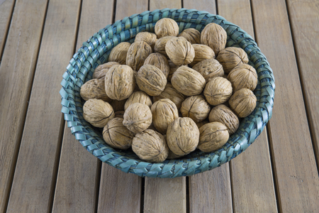 Walnuts in the basket on wooden background.