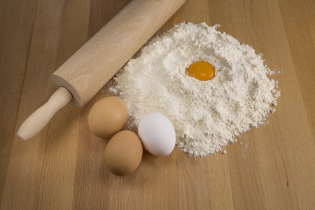Eggs and flour on a wooden board. Stock Photo