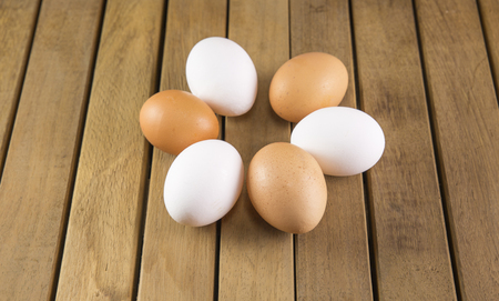 Fresh farm eggs on a wooden background. Stock Photo