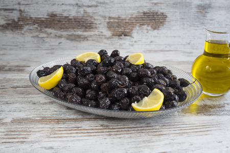 Black olives and olive oil on a wooden table. Stock Photo