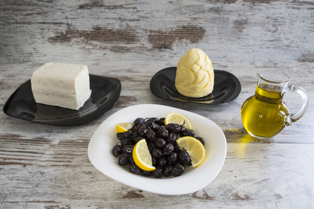 White cheese, butter, olive oil and black olive on white wooden ground. Stock Photo