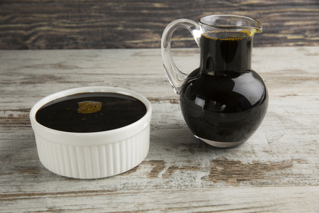 molasses: Grape molasses in bowl and glass pitcher on wooden background.