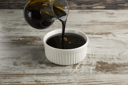 syrup: Grape molasses flowing from the glass pitcher on wooden background.