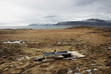 Woman scenic ocean panorama natural outdoor hot tub bathtub spring thermal pool Djupavogskorin in Djupivogur Iceland