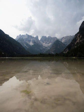 Panorama reflection of Dolomites mountains in alpine lake Duerrensee Durrensee Lago di Landro Trentino South Tyrol Italy