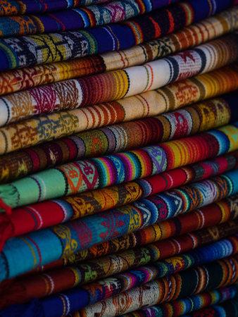 Textile pile colorful traditional andean indigenous handmade woven Otavalo handicraft market Ecuador South America Reklamní fotografie