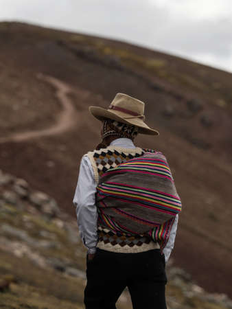 Man in traditional andean indigenous clothes at colorful Palccoyo rainbow mountain Palcoyo Cuzco Peru South America