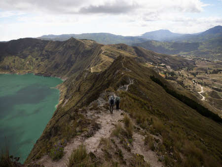 Hikers walking on andean volcano caldera crater lake Quilotoa rim ridge loop in Pujili Cotopaxi Ecuador andes South America