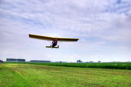 airstrip: Experimental microlight taking off from a grass airstrip Stock Photo