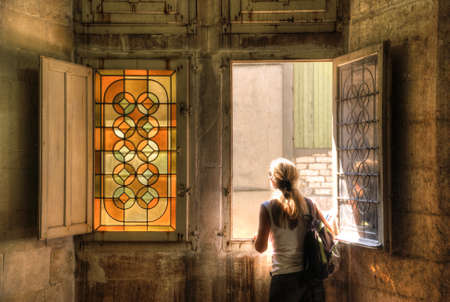 stained glass window: A girl seen from behind facing outside St. Trophime Cloister near a stained glass window