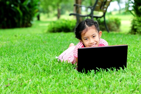 Young girl smiling with a laptop on green grass photo