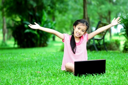 Young girl with a laptop sitting on green grass photo