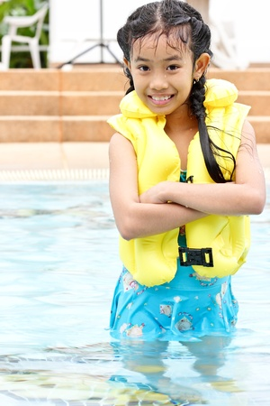 Cute young girl standing in a pool photo