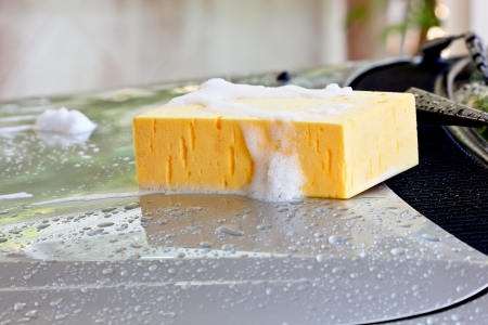 スポンジや車の洗浄のシャンプーが付いている車を洗う