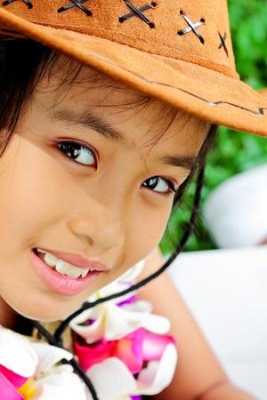 Cute asian girl wearing a cowboy hat looking at  the camera photo